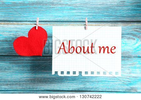 Blank paper hanging on rope on blue wooden background, about me