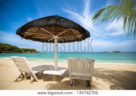 tropical beach, perfect place for relaxing, sun recliner in the shade of a palm tree