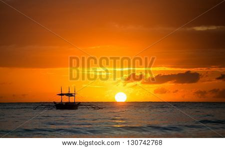 Sailboat sunset fantasy with a silhouetted boat sailing along against a vivid colorful sunset orange and yellow color filled sky.
