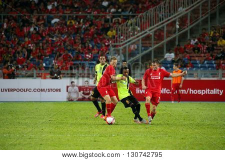 July 24, 2015- Shah Alam, Malaysia: Liverpool's players (red) challenge for the ball against a Malaysian defender in the friendly match against Malaysia. Liverpool FC from England is on an Asia tour.