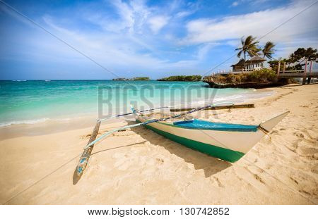 Philippines traditional fishing boat in the clear sea waters on the blue sky background with shining sun