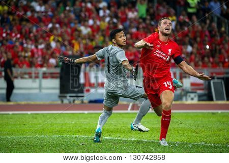 July 24, 2015- Shah Alam, Malaysia: Liverpool's Jordan Henderson (red) challenges for the ball in a friendly match against the Malaysian team. Liverpool Football Club from England is on an Asia tour.
