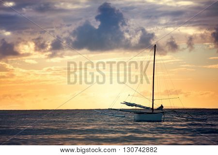 fishing boat sailing alone at sea over beautiful sky