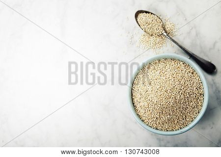 bowl of healthy white quinoa seeds  on white marble background