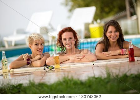 Three nice female bathers standing in front of railing of pool with bottles of refreshing drinks
