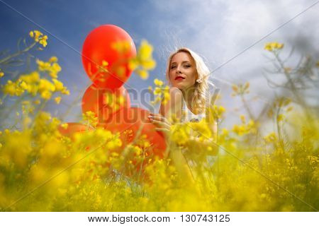 Portrait of young girl in yellow flowers with balloons