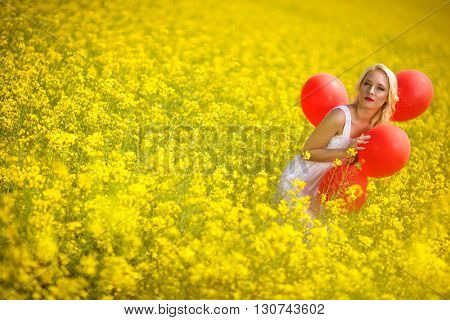 young lady in blossom raps field with balloons