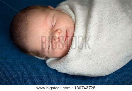 Adorable little baby sleeping and smiling, sweet dream