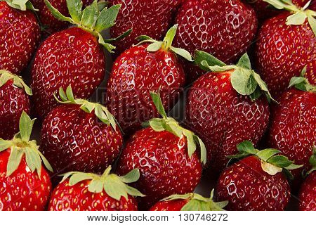 Strawberry background of whole strawberries. Colorful ripe strawberries. Fruit background. Strawberry pattern. Spring summer background. Macro. Texture.