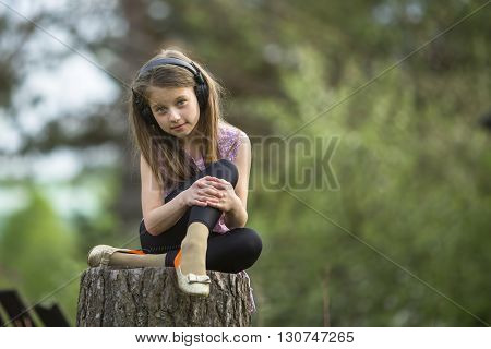 Cute girlie with headphones sitting on a stump near the country house.