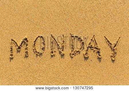 Monday - written by hand on a golden beach sand.