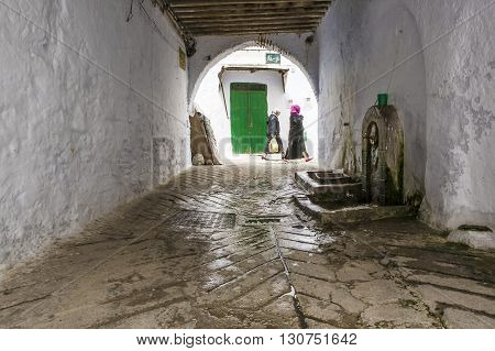 TETOUAN MOROCCO - AUGUST 17: Unidentified arabic women walking by whitewashed streets of the medieval medina on August 17 2014 in Tetouan Morocco
