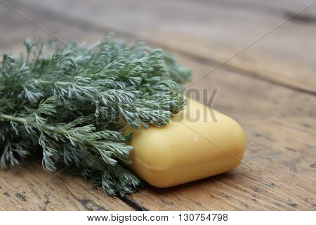 Natural handmade soap and tarragon on a wooden board