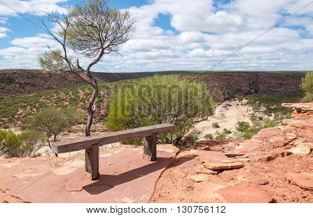 Wooden resting bench on a red sandstone bluff overlooking the Murchison River gorge with native plants in Kalbarri National Park in Western Australia.