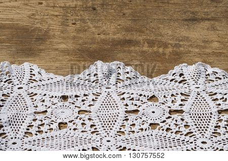 Background of a wooden table and a white crocheted napkin