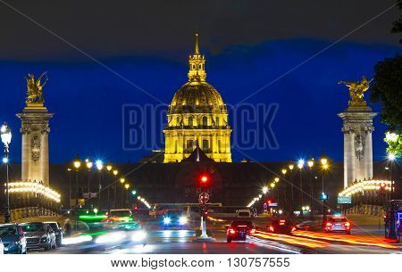 The Invalides museum and Alexandre III bridge at night Paris France.