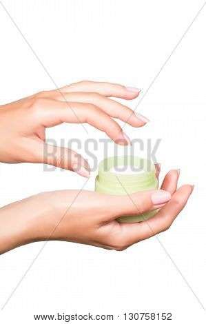 Female manicured hands holding cream jar isolated on white background