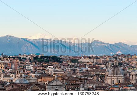 Aerial view of Rome Italy downtown at sunset with mountains on the background. View from above on historic centre with roofs and Domes
