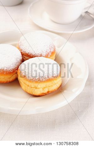 three doughnuts on white plate over table