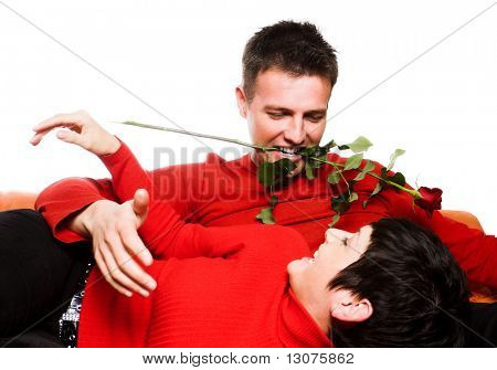 This is a happy moment. A young couple is having a date and the man tries to be very romantic and seductive. He keeps a rose between his teeth and the woman finds this very funny and she laughs.