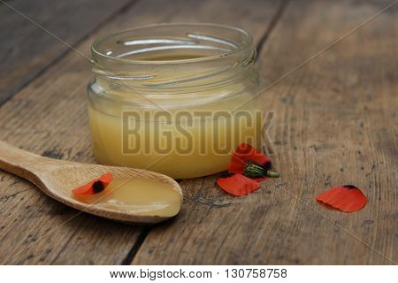 Natural honey in a glass jar and a wooden spoon.