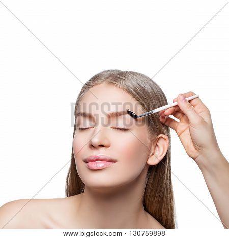 Beautician correcting eyebrows form on beautiful woman face. Beauty shot. Close-up. I
