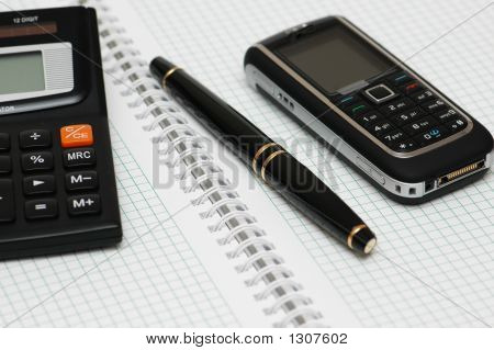 Calculator, Ballpen And Mobile Phone On The Notebook