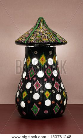 Illuminated black painted perforated pottery table lamp
