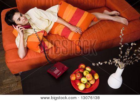 Mulheres jovens está descansando no sofá e receber uma chamada de telefone.