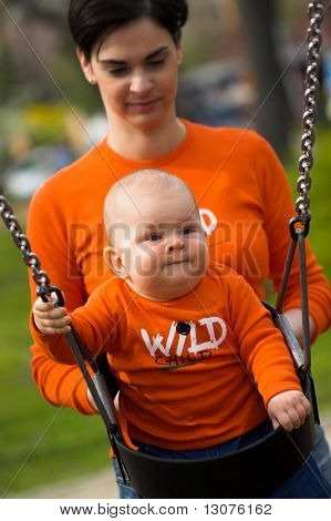A 9 months old baby and his mother are swinging together on the playground. They are wearing a similar orange T-shirt.