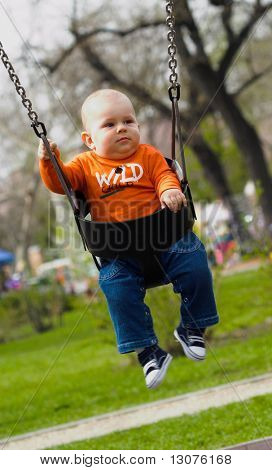 Baby is swinging on a playground.