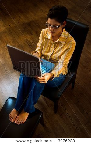 Young women is working on a laptop computer in home environment.