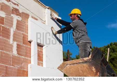 worker mounts sheets of polystyrene on external vertical walls. Hand motion blur.