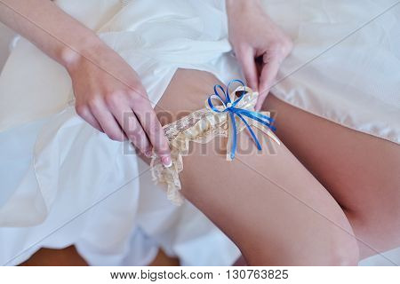 Beauty bride in dressing gown is wearing bridal garter indoors. Beautiful model girl in colorful wedding clothes. Female portrait of cute lady in dress. Close-up arms of woman
