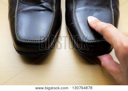 Thumb pressing down on head of brown leather shoe on wooden floor. Focus on finger.