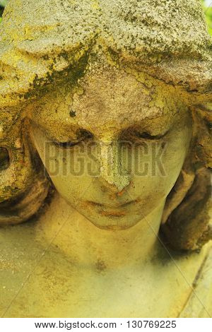 Vintage image of a sad angel on a cemetery (fragment of antique statue)
