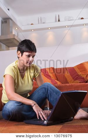 Young woman is sitting on the floor and using a laptop computer. Maybe she is surfing the net, chatting or studying for the next university exam.