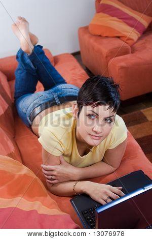 Junge Frau ist liegt und Ausruhen auf dem Sofa und einen Laptopcomputer zu verwenden. Vielleicht ist sie surfen die