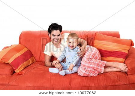 Baby and mother are playing together on the sofa. They are wearing pajamas.