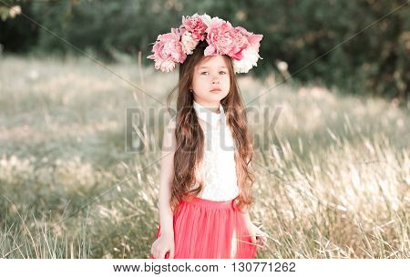 Cute kid girl 4-5 year old wearing stylish peony hairband outdoors. Looking at camera. Childhood.