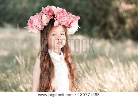 Beautiful baby girl 3-4 year old with flower hairband posing outdoors. Looking at camera. Summer season.