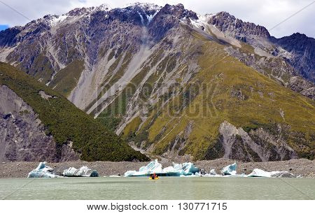 Boat on a glacial lake in front of icebergs and with snow capped mountains behind