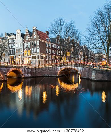 A view of the bridges at the Leidsegracht and Keizersgracht canals intersection in Amsterdam at dusk. Trails from traffic can be seen on the bridge