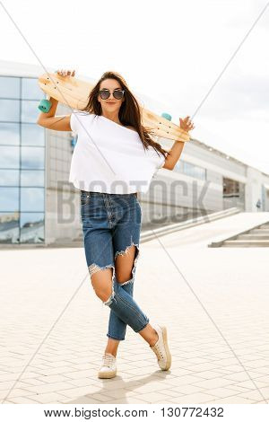 Happy woman in fashion sunglasses casual white t-shirt and ripped jeans stay with her wooden longboard skateboard in front of business or sport building. Cute lady have fun and smile to the camera.