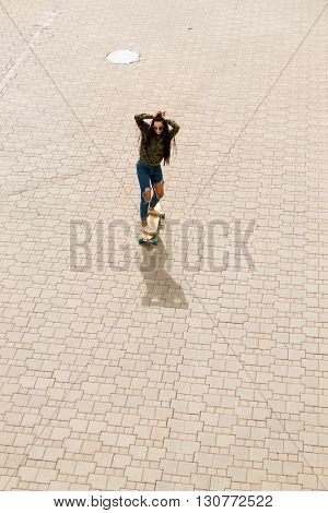 Happy beautiful girl with long healthy hair in fashion sunglasses casual clothing ride on wooden longboard skateboard. Cute hipster touch her hairs. Urban scene city lifestyle. Top view from above.