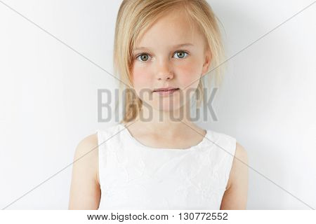 Close Up Shot Of Cute Fashionable Child With Green Eyes And Blonde Hair Weraing White Dress, Looking