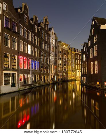 A view of buildings along the canals in Amsterdam in the Centrum Borough and De Wallen Area. Taken at Night. There is space for text.