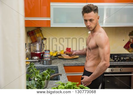 Side view of sexy muscular topless man in black apron making coffee for breakfast in kitchen