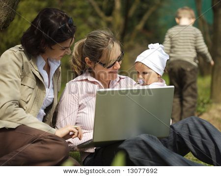 Young mothers are sitting on the ground in the garden and using a laptop.