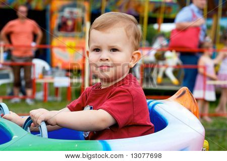 Two years old child driving toy vehicle in the amusement park.